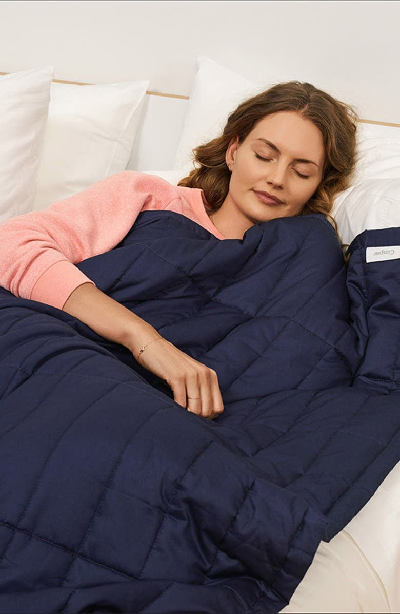 model with the dark blue quilted blanket over them