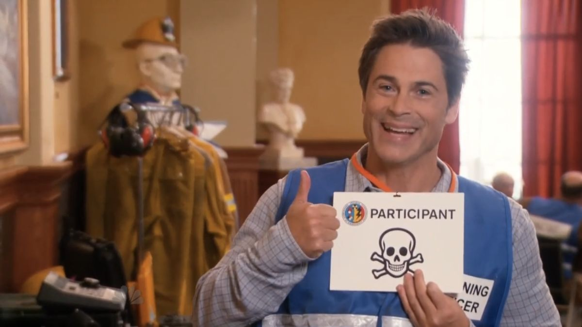 Chris Traeger smiles and gives a thumbs up while holding a participant sign with a skull on it