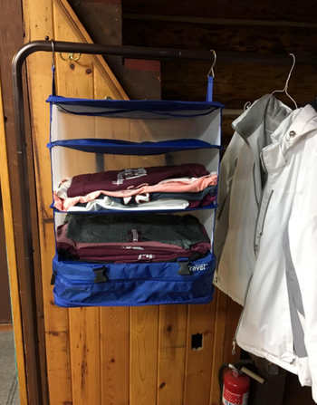 reviewer image of shelf hung on door frame with shirts folded on each shelf