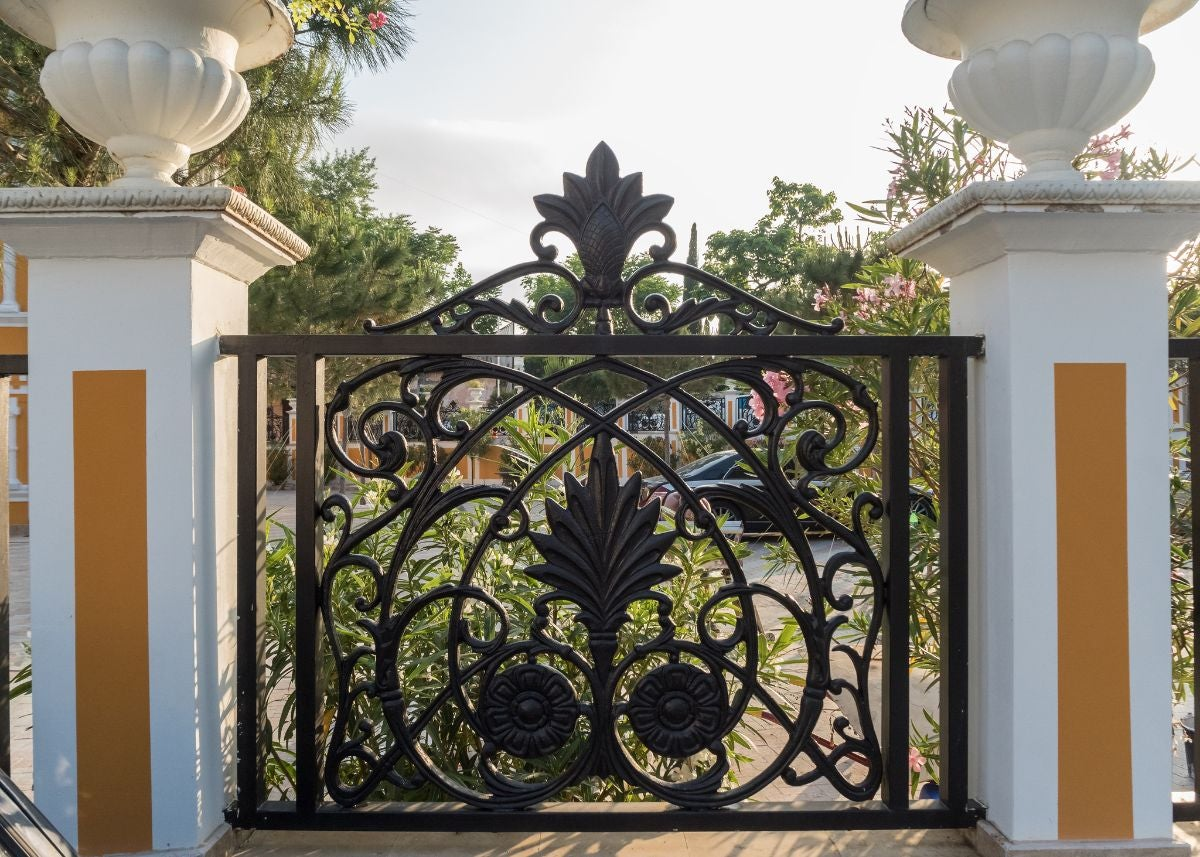 A iron gated entryway with stone columns beside it