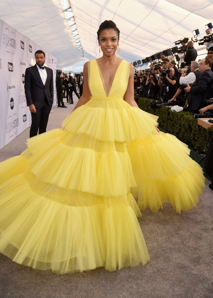 Susan Kelechi Watson wearing a tiered tulle gown with a plunging neckline