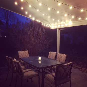 the lights above an outdoor dining table