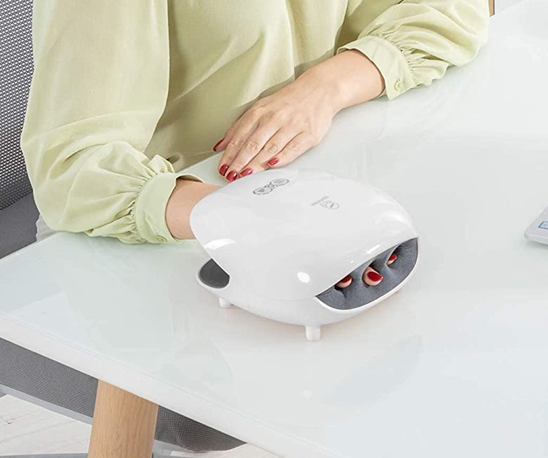Model with their hand in a white device with slots for fingers