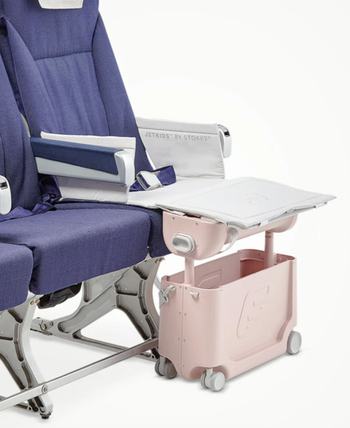 the suitcase in front of a seat that looks like an airplane chair, with it raised up, creating a leg rest for kids to make the seat more comfortable
