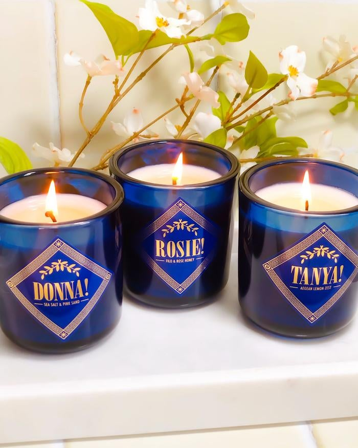 the blue candles with each lady's name and scent written on them in Mamma Mia-inspired font