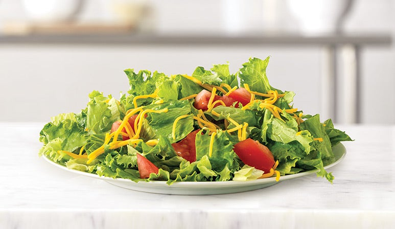 a salad with shredded cheese, lettuce, and sliced tomatoes