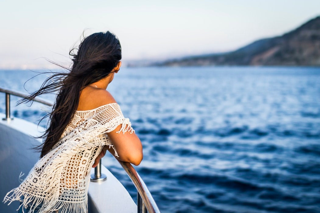 """Woman leaning on the boat railing while """"looking forward to the land or looking back at the sea"""""""