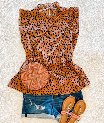 top laid out and styled on bed with denim shorts, sandals, and a purse