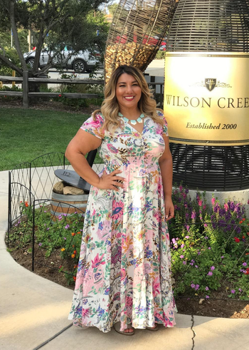 A reviewer wearing the dress in white with bright tropical flowers