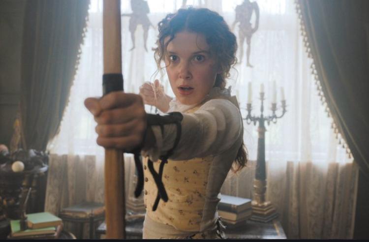 A young girl wearing a dress wields an arrow