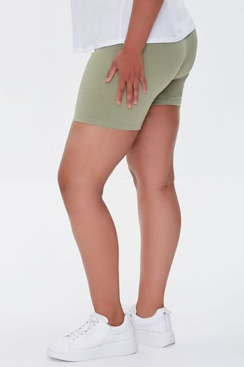 same model wearing the shorts in green