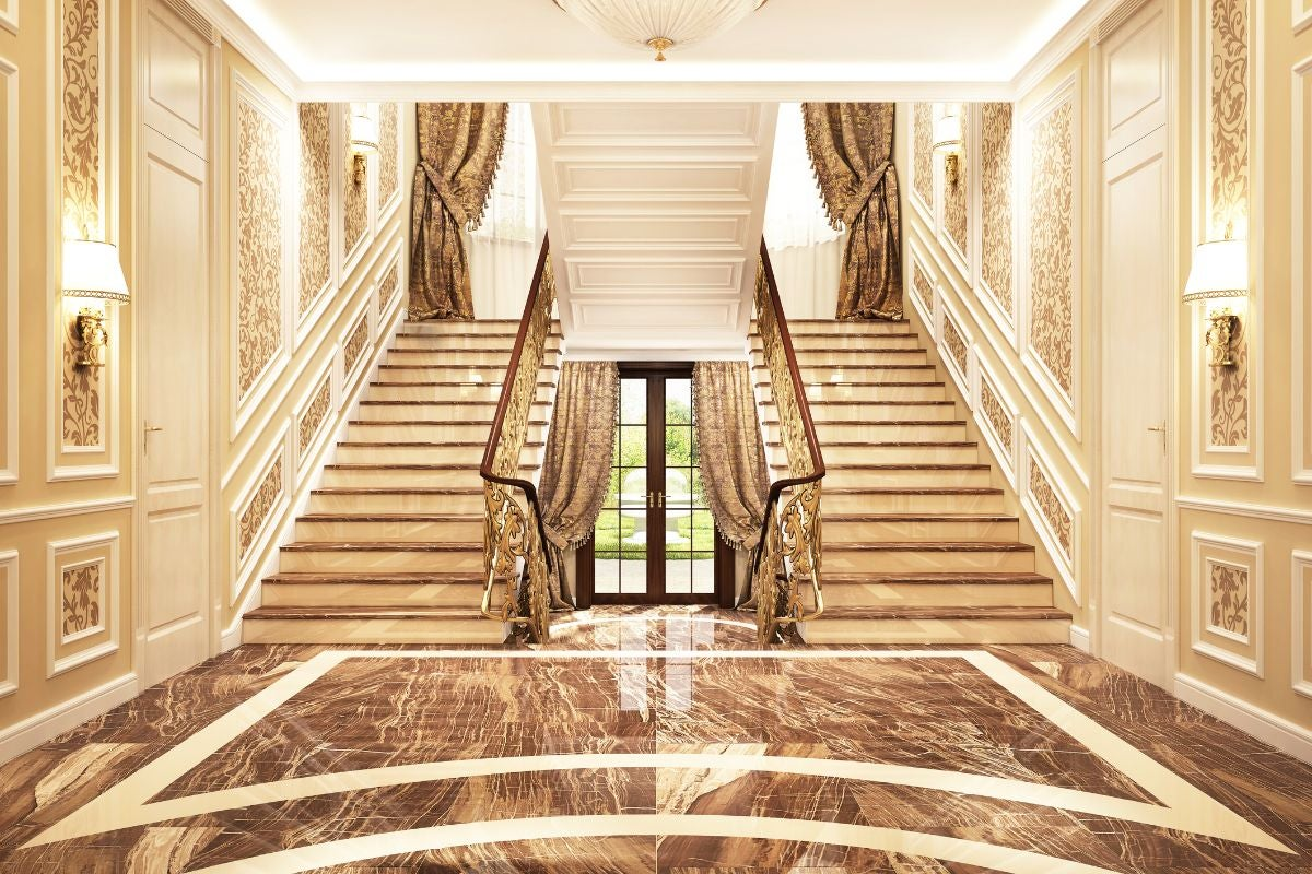 A grand entryway with two staircases on either side of the back door and golden details all around