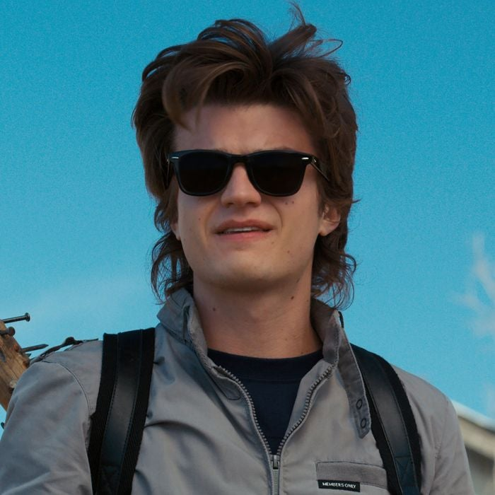 Steve is wearing a jacket, backpack, and sunglasses while slightly smiling