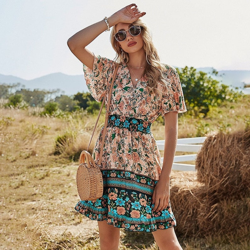 model wearing the pink and blue floral mini dress with flutter sleeves and an elastic waist