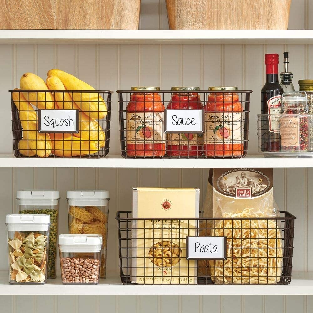three baskets in a pantry holding pasta, sauce, and squash