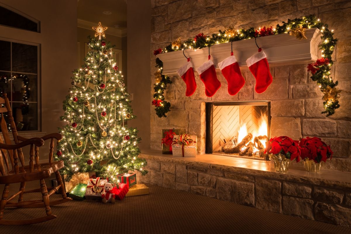 A classy, classic Christmas tree in a living room next to a fireplace with a roaring fire