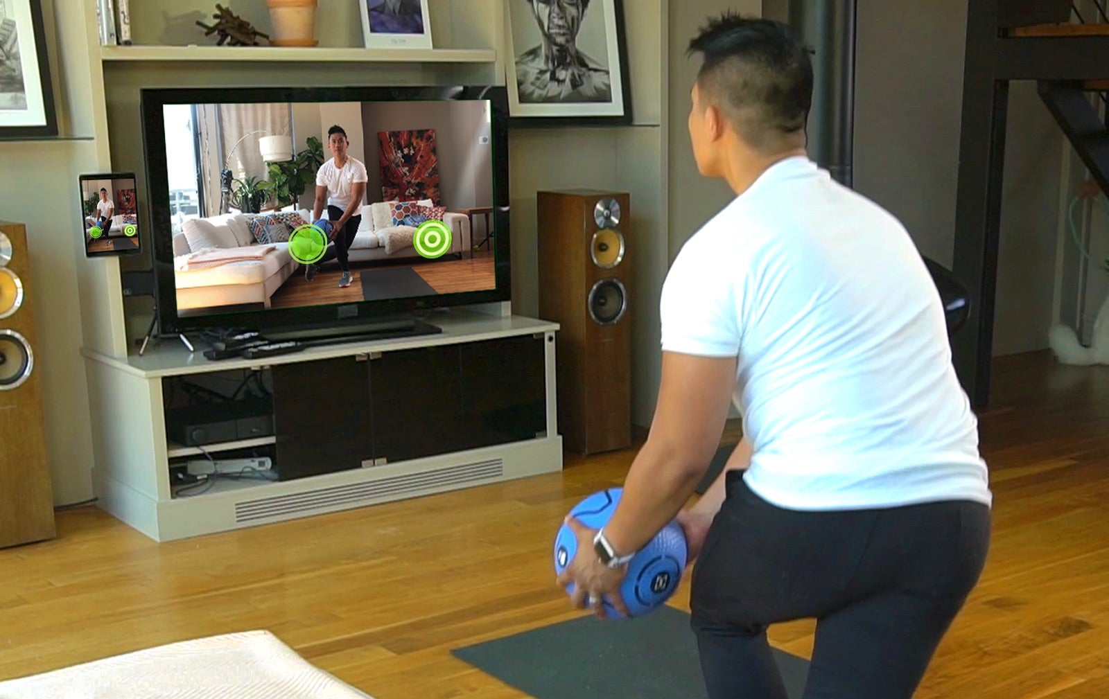 person using smart ball in living room with themselves on the screen to show where they should move the ball