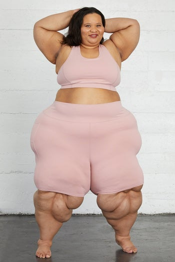 Model in a pair of blush pink knee length compressive bike shorts