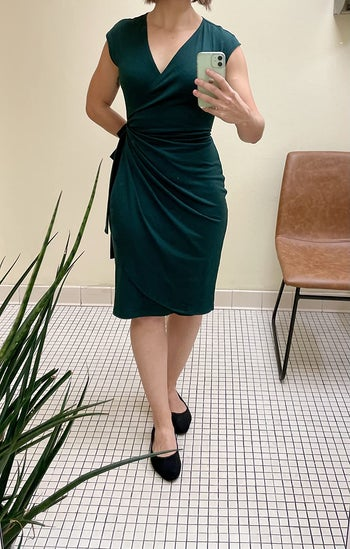 reviewer wearing the green dress with black flats