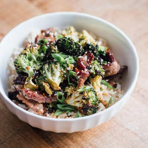 Rice bowl with meat, broccoli, green onions and sesame seeds