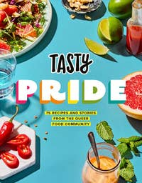 cookbook cover for Tasty Pride with a tabletop full of assorted food and drinks
