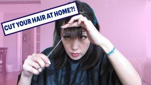 A hairdresser cutting her own bangs.