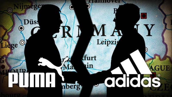 The logos of Puma and Adidas are over an image of black silhouettes of two men shaking hands with a map projection behind them of Germany being torn in half.