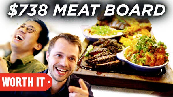 Steven and Andrew laugh next to a picture of a giant meatboard with lots of meat and side dishes.