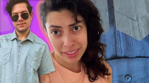 The video subject, Claudia, looks at the camera with a worried expression. To her left, a co-worker, Ivan, wears the finished version of the shirt, with samples of the shirt fabric to Claudia's right.