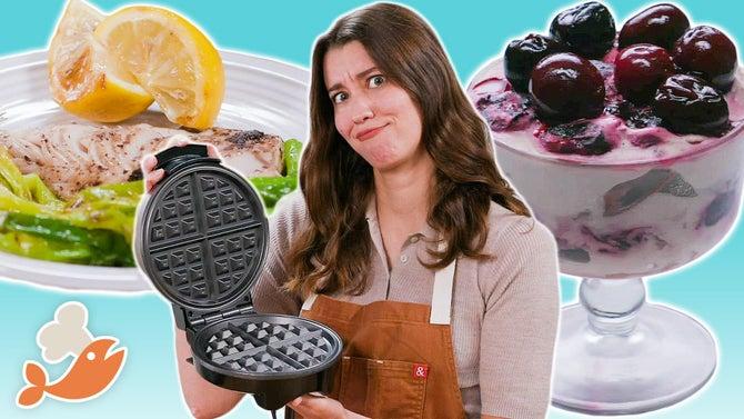 亚历克西斯扬起手中的华夫饼干的铁疑惑的脸。樱桃果仁蛋糕和吃饭的一些照片是在她的身后。