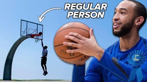 basketball player aiming for the basket while a man hangs from the rim