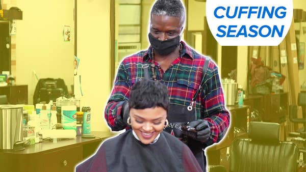 A barber cuts a woman's hair