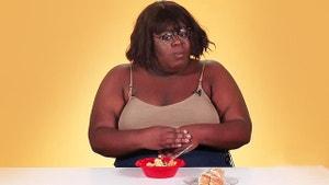 A woman eats Soup Joumou