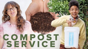 Two women smiling, one holding a compost bin. A hand full of compost in the center.