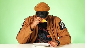 Michael Harvey takes a bite of a beef patty while blindfolded.