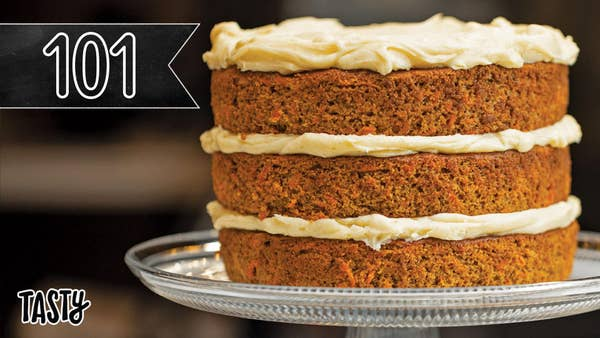 The entire finished carrot cake on a cake stand. Tasty logo and 101 banner on the left side